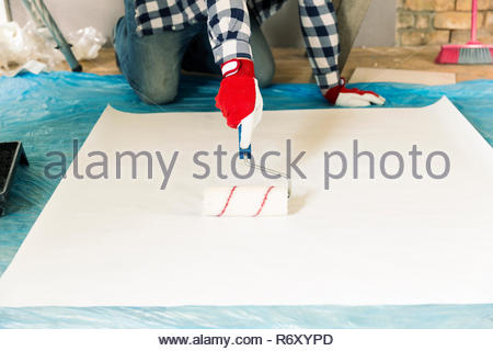Repair, building and home renovation concept - close up of male hands smearing wallpaper with glue and roller - Stock Photo