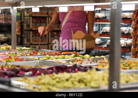 Lady choosing healthy foods at a grocery salad bar is one of the best things to do in living a better lifestyle. - Stock Photo