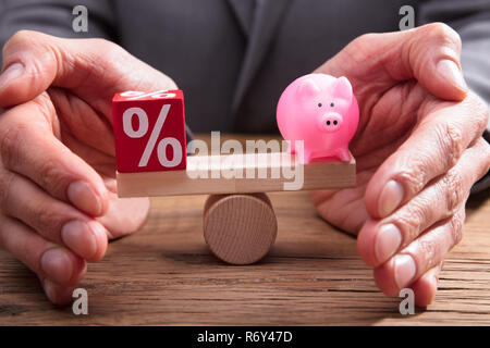 Human Hand Protecting Balance Between Percentage And Piggybank - Stock Photo