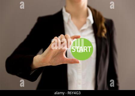 Young businesswoman holding virtual button start. New start, beginning, business concept
