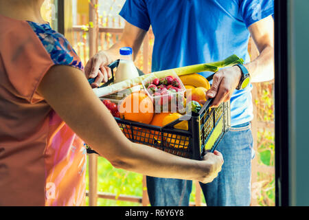 woman accepting groceries box from delivery man at home - Stock Photo