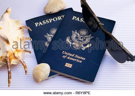 travel flat lay united states passports with sunglasses and seashells on white cardboard background - Stock Photo