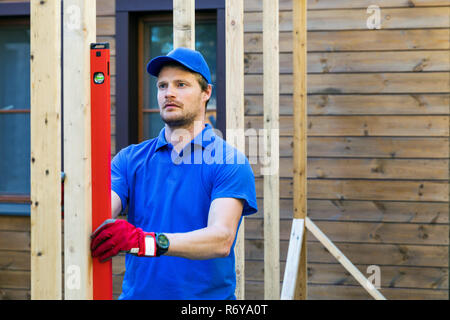 worker check the level of wooden house structure - Stock Photo
