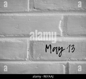 May 13  WORDS WRITTEN ON WHITE PLAIN BRICK WALL - Stock Photo