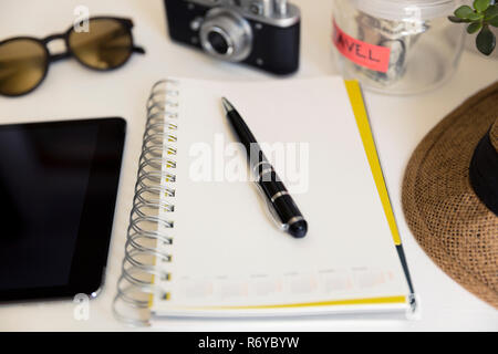 Travel planning concept on table. Traveler's accessories and items with notebook and money saving jar, sunglasses and hat - Stock Photo