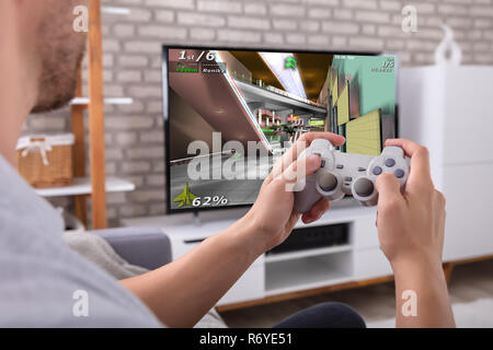 Close-up Of A Man With Joystick Playing Game On Television - Stock Photo