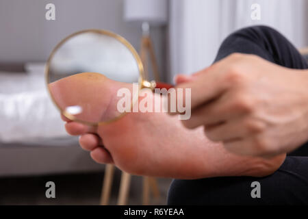 Close-up Of A Man's Hand Holding Magnifying Glass In Front Of His Feet - Stock Photo