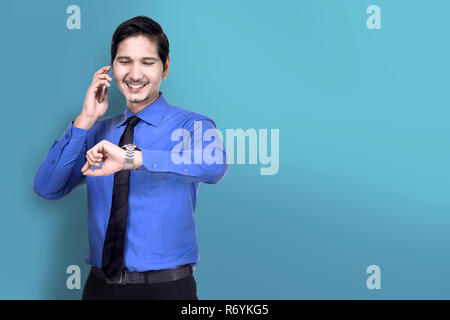 Smiling asian businessman check the watch while talking on phone - Stock Photo