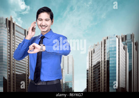 Handsome asian businessman using phone and check the watch - Stock Photo