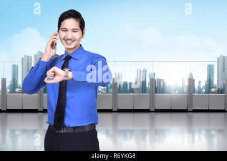 Happy asian businessman with phone checking the watch - Stock Photo