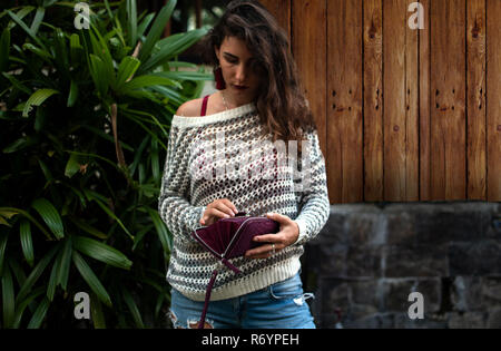 Woman holds a purple python purse in her hands. money and shoping. Woman's hands with wallet, nature background, palms leaves, wood, wearing jeans, fashion style - Stock Photo
