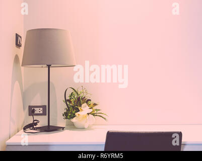 Working desk with table lamp,  bedroom interior. Filtered pink tone color image. - Stock Photo