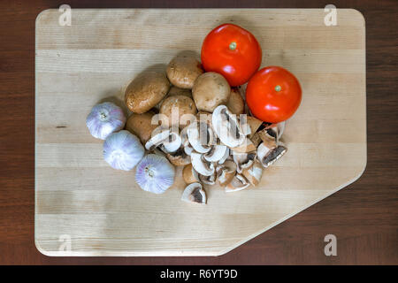 Tomatoes Garlic and Portobello Mushroom on Cutting Board - Stock Photo