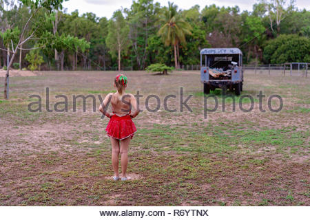 Young girl in a dance costume with hands on hips looking out towards and old car - Stock Photo