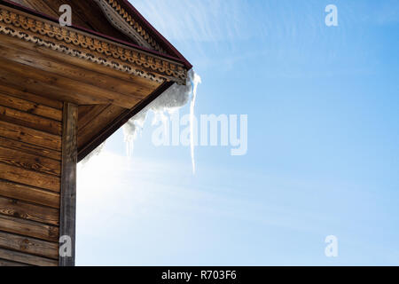 icicle on roof of old wooden house in Suzdal - Stock Photo
