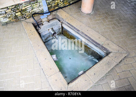 A small swimming pool with holy water from the spring. A niche in the floor for recruiting water from a source - Stock Photo