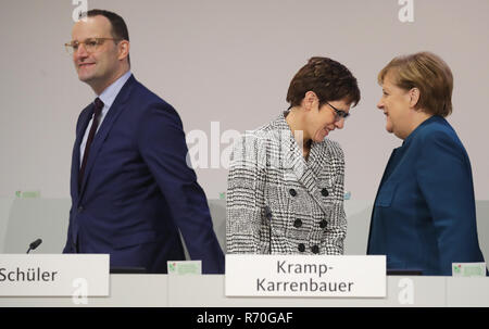 Hamburg, Germany. 07th Dec, 2018. The candidates for party chairmanship, Jens Spahn (l-r), Annegret Kramp-Karrenbauer and German Chancellor Angela Merkel (CDU), will stand together on stage at the CDU federal party conference. The delegates elect a new party chairman in the afternoon. Credit: Kay Nietfeld/dpa/Alamy Live News - Stock Photo