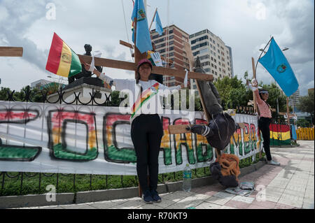 La Paz, Bolivia. 06th Dec, 2018. Demonstrators chained to a wooden cross in front of the Supreme Electoral Court are protesting against the Court's decision to allow another candidacy for long-term president Morales. Credit: Marcelo Perez del Carpio/dpa/Alamy Live News - Stock Photo