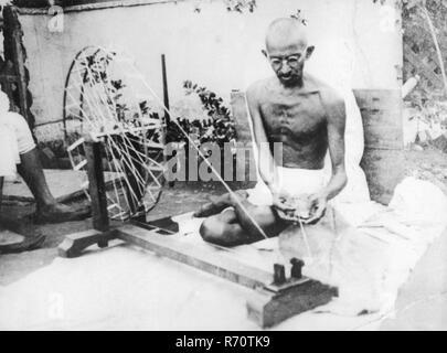 Mahatma Gandhi spinning with charkha, - Stock Photo