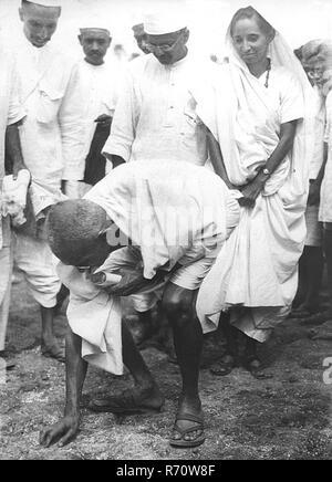 Mahatma Gandhi breaking salt law by picking up lump of natural salt at Dandi, Gujarat, India, April 6, 1930, 8.30 a.m.