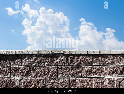 Wall and sky. A dark brick wall against the background of a light sky with clouds. Symbols of despair and freedom. - Stock Photo