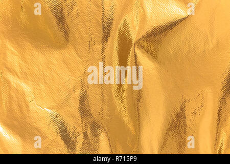 Highly detailed texture of a rusty golden yellow shimmering thermal blanket background. - Stock Photo