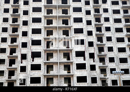 Front view of high-rise modern apartment building construction in process front view horizontal - Stock Photo