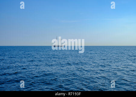 The sailing ship, the schooner BANJAARD, sails over the water on the horizon. - Stock Photo