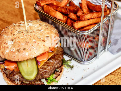 Tasty Cheese-Burger with homemade sweet potato chips in a small net basket - Stock Photo