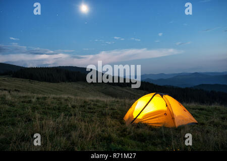 Illuminated orange tent in the mountains at dusk. The tent is lit from the inside. In the sky, the moon and the stars - Stock Photo