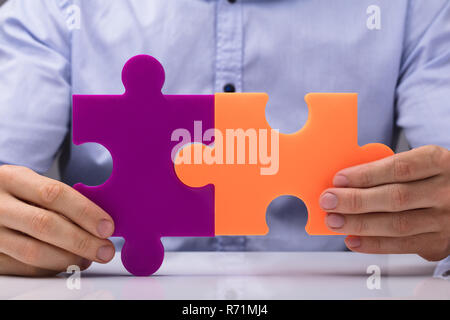 Person Holding Two Jigsaw Puzzle - Stock Photo