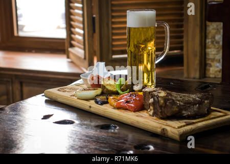 beef steak and a mug of beer on the wooden table in the pub - Stock Photo