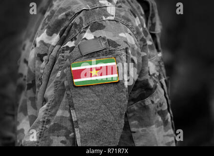Flag of Suriname on soldier arm. Flag of Suriname on military uniforms (collage). - Stock Photo