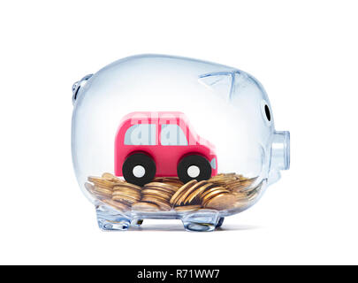 Car toy on coins inside transparent piggy bank with clipping path - Stock Photo