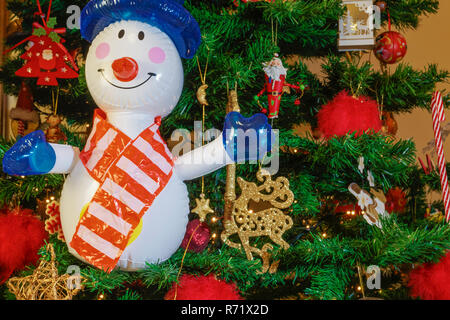 Large inflatable snowman on a Christmas tree. Air blown seasonal figure before an illuminated artificial Christmas tree with lights and decorations. - Stock Photo
