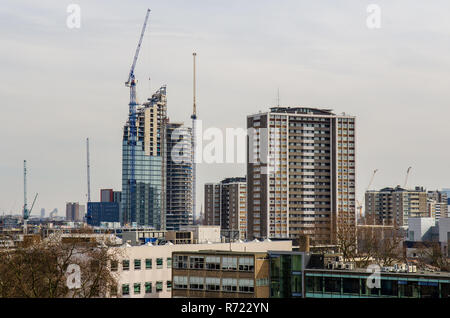 London, England, UK - March 13, 2015: Tower cranes stand over the construction sites of skyscrapers, part of a cluster of new-build high-rise apartmen - Stock Photo