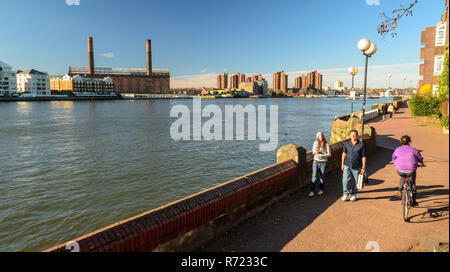 London, England, UK - March 16, 2014: Pedestrians and cyclists enjoy a sunny day on Battersea Riverside, with the River Thames and Chelsea's Lots Road - Stock Photo