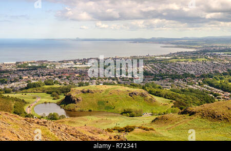 Houses of Portobello, Musselburgh, Presponpans and Cockenzie line the Firth of Forth Coast as viewed from above Dunsapie Loch on Arthur's Seat hill in - Stock Photo
