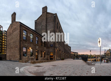 London, England, UK  November 21, 2018: The sun sets behind the Victorian brick Coal Office, once part of the King's Cross railway work and now a shop - Stock Photo