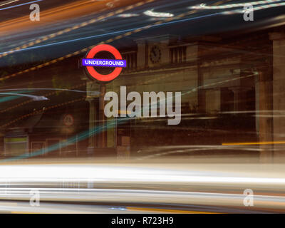 London, England, UK - October 15, 2018: Traffic leaves light trails at night outside Hyde Park Corner tube station in London. - Stock Photo