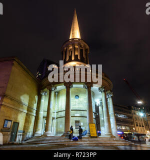 London, England, UK - October 12, 2018: Pedestrians and traffic pass All Souls Church, illuminated at night, at the head of London's Regent's Street. - Stock Photo