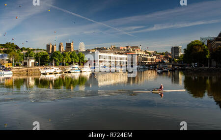 Bristol, England, UK - August 11, 2018: A rower trains in Bristol's Floating Harbour docks on a summer morning, while hot air ballons float over the c - Stock Photo