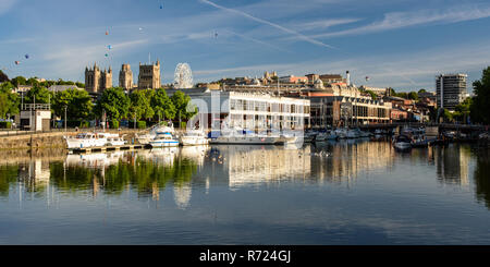 Bristol, England, UK - August 11, 2018: Hot air balloons float over the cityscape of Bristol as viewed from the Harbourside. - Stock Photo