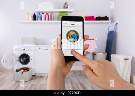 Close-up Of A Woman's Hand Operating Washing Machine With Cellphone - Stock Photo