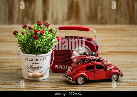 Artificial Flower, Vintage Radio and Red Toy Car on Wooden Background - Stock Photo