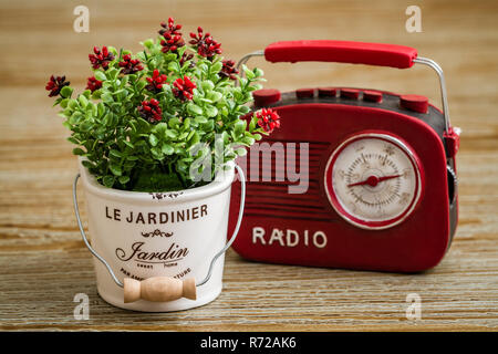 Artificial Flower, Red Vintage Radio on Wooden Background - Stock Photo