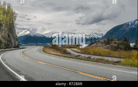 Alaska Scenic Road:  The Seward Highway curves beneath cloudy skies as it passes by snow-covered mountains at the edge of an ocean inlet south of Anchorage. - Stock Photo