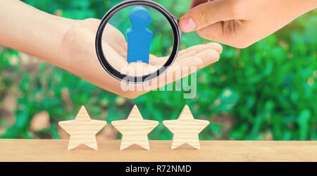 The hand holds a human figure and three stars. The concept of a business leader and a skilled manager. Success and achievement. Increase of efficiency - Stock Photo