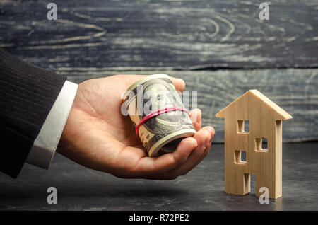 Wooden house and money in hand. A loan secured by real estate. Home renovation and repair. Warm loans. Buying and selling homes. Affordable housing. T