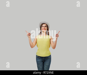 Casual woman pointing up - Stock Photo